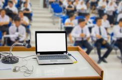 Computer on the table and group students blur sitting in the a classroom.  royalty free stock images