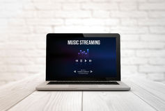 Computer on a table music streaming. Streaming concept: digitally generated laptop on a wooden table showing music streaming. Screen graphics are made up. 3d vector illustration