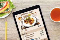 Computer tablet with app delivery food screen on wooden table Stock Photo