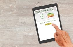 Computer tablet with with credit report and freeze button. Computer tablet or smartphone with credit score report and senior hand about to press button to freeze royalty free stock image