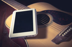 Computer tablet on guitar. Royalty Free Stock Photos