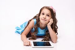 Computer tablet. Little girl. Modern technologies. White background. Brown hair royalty free stock images