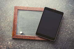 Computer tablet and old chalkboard Stock Photography