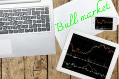 Computer, tablet, smartphone and paper with text bull market on Royalty Free Stock Images