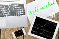 Computer, tablet, smartphone and paper with text bull market on Stock Image