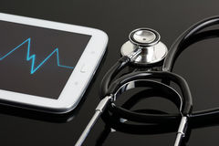 Computer tablet and stethoscope. A computer tablet and stethoscope on a reflective black background Royalty Free Stock Image