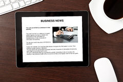 Computer tablet is on the table with business news on screen Royalty Free Stock Photos