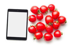 Computer tablet and tomatoes royalty free stock photos