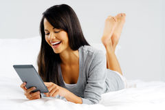 Computer tablet woman. Woman reading a modern computer tablet device while lying in bed happy and smiling Royalty Free Stock Image