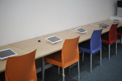Computer tablets in a classroom. Computer tablets on a long desk in a classroom Royalty Free Stock Photo