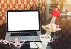 Computer, taccuino, o computer portatile dello schermo in bianco sul contatore con la tazza o Fotografia Stock