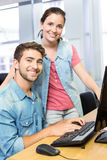Computer teacher helping pretty female student Stock Photo