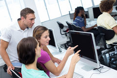 Computer teacher helping pretty female students. In his class Royalty Free Stock Photos