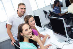 Computer teacher and pretty female students Stock Photo