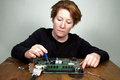 Computer Technician. Female computer technician performing upgrades to a computer motherboard Stock Images