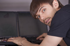 Computer technician with laptops. Computer technician in black shirt typing on laptops Royalty Free Stock Photography