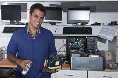 Computer technician with motherboard at workshop Stock Photography