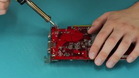 Computer technician soldering video card Stock Photo