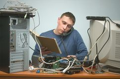 Computer technician specialist. PC repairman. Computer technician engineer holding in hands a manual computer guide book and speaks on the phone. PC repairman Stock Photography