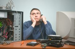 Computer technician specialist. PC repairman. Tired computer technician is consulting a users by their questions by the phone. PC repair service center Stock Photo