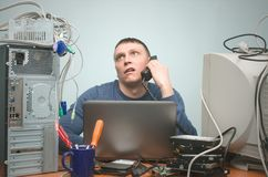 Computer technician specialist. PC repairman. Tired computer technician is consulting a users by their questions by the phone. PC repair service center Stock Image