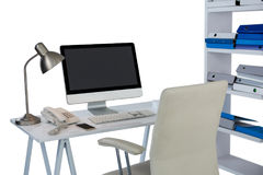 Computer with telephone and mobile phone at desk. Against white background Stock Photography