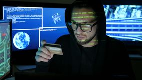 Computer terrorism, steal finances through the internet, criminal hacker cracking banking system, hacker holds in hands. Computer Terrorism, steal finances