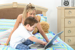 Computer Time. Mother and son working on computer together in bed Stock Images