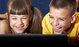 Computer Time. Boy and girl (7-10) using laptop Royalty Free Stock Photos
