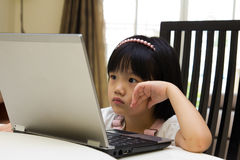 Computer time at home. Little girl is playing with a computer Royalty Free Stock Photo