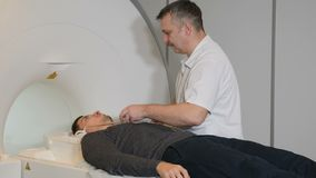 Computer tomography concept. Health concept. Person gets scanned by magnetic resonance imaging scanner in modern. Hospital.Male radiology specialist in white stock footage