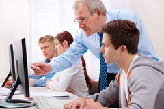 Computer training. Students with a teacher in computer classroom Royalty Free Stock Photo
