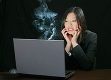 Computer trouble for asian girl. Young attractive asian woman working on a laptop computer Royalty Free Stock Photo
