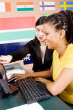 Computer tutor. A chinese computer tutor helping an african american woman with her studies royalty free stock image