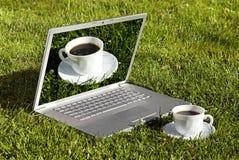 Computer und Kaffee auf dem Gras Stockfotografie