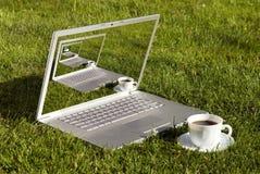 Computer und Kaffee auf dem Gras Lizenzfreies Stockbild