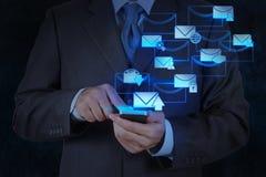 Computer van de het gebruiks de slimme telefoon van de zakenmanhand met e-mailpictogram Stock Foto