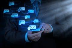Computer van de het gebruiks de slimme telefoon van de zakenmanhand met e-mailpictogram Stock Foto's