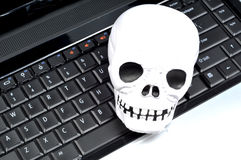 Computer virus. Human skull on keyboard depicting virus stock photos