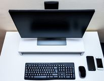 Computer wireless mouse, black monitor, keyboard and two mobile phones on a white desk. Minimal computer setup Royalty Free Stock Photos