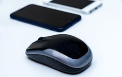 Computer wireless mouse and two mobile phones  on a white desk. Computer wireless mouse and two mobile phones on a white desk. Minimal computer setup Stock Images