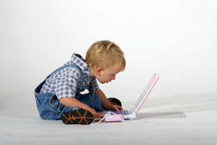 Computer work. Cute toddler boy sitting on the floor working on a computer Stock Photos