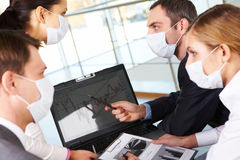 Computer work. Serious business partners in protective mask looking at screen of laptop in working environment royalty free stock photo