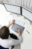 Computer work. A designer working behind two monitors, using a keyboard and a graphic tablet Stock Photography