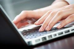 Computer work. Image of human hands pressing keys of laptop Royalty Free Stock Image