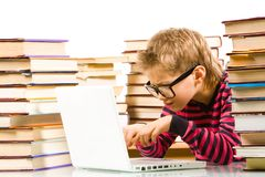 Computer work. Portrait of pensive lad in eyeglasses typing on laptop between piles of books Royalty Free Stock Photo