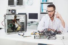 Computeringenieur die gebroken apparaat bekijken en een telefoongesprek maken stock afbeelding