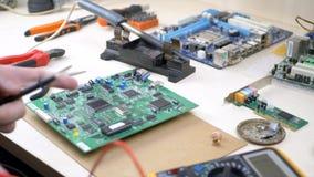 Computeringenieur die met meetapparaat motherboard onderzoeken stock video