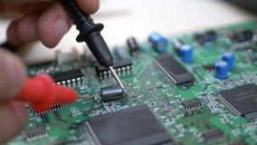 Computeringenieur die met meetapparaat motherboard onderzoeken stock videobeelden