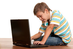Computerised child. A closeup profile portrait of a seven-year-old kid working with a laptop; isolated on the white background Stock Image